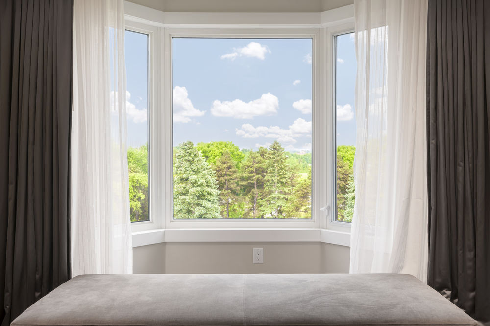 Bay window with drapes, curtains and view of trees under summer sky (Bay windows vs bow windows)