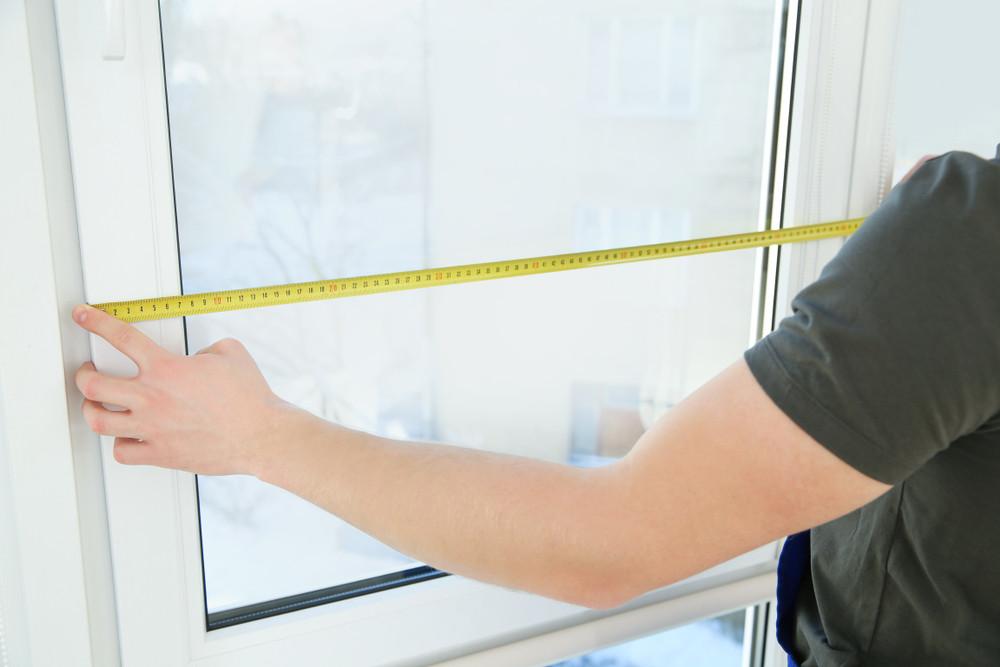 Man measuring his window (Standard Size VS Custom Built Windows)
