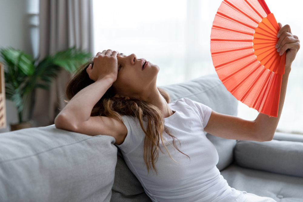 Lady hot in summer heat inside home (How Replacement Windows Can Keep Your Home Cool in the Summer)